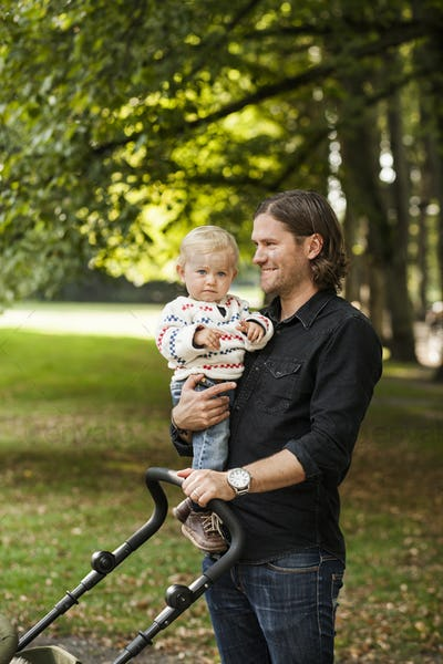 Portrait of baby girl carried by father in park