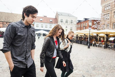 Friends walking at town square in city