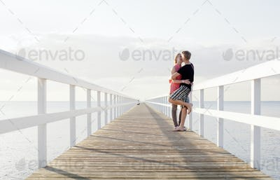 Full length of romantic young couple kissing on pier