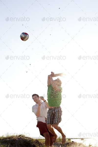 Young male friends playing volleyball against clear sky