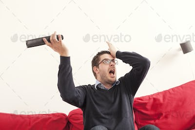 Shocked man holding remote control while sitting on sofa against white wall at home