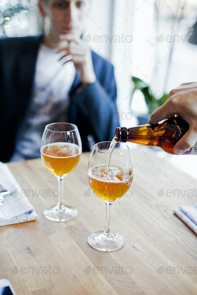 Cropped hand of man pouring beer in glass with partner sitting at restaurant