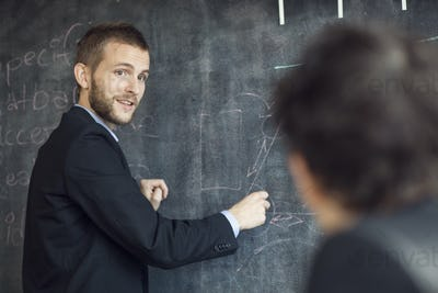 Side view of confident businessman giving presentation at creative office