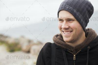 Happy man looking away at lakeshore