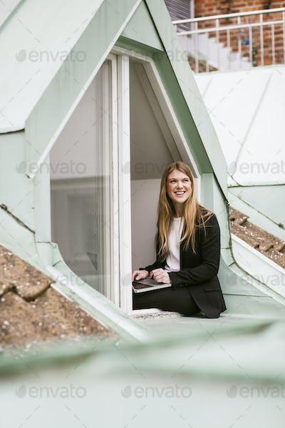 Beautiful businesswoman sitting with laptop on window sill