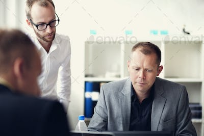 Concentrated businessmen during meeting in office