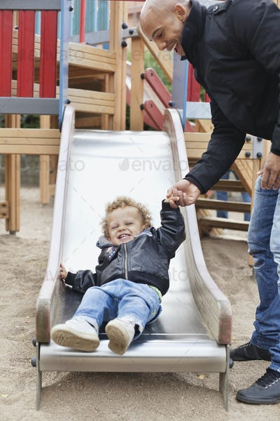 Happy father assisting son on slide at playground
