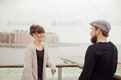 Happy business people standing on building terrace by river against sky