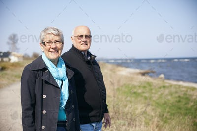 Portrait of senior couple standing at sea shore on sunny day