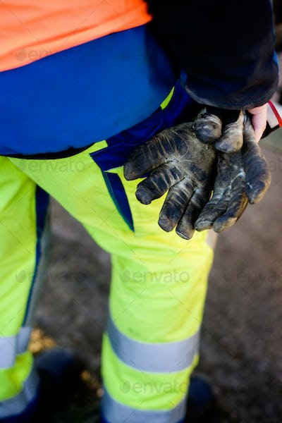 Low section of construction worker holding messy gloves