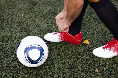 Low section of player wearing shoe on soccer field