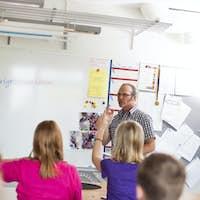 Mature teacher explaining to junior high students in classroom