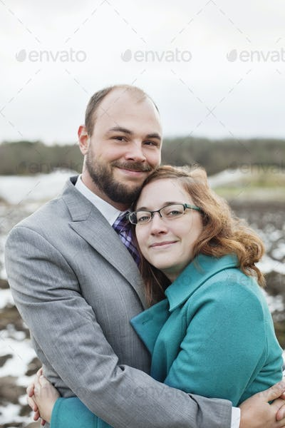 Portrait of smiling young couple embracing outdoors