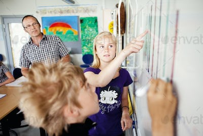 Girl pointing at chart on whiteboard with boy and professor looking in classroom