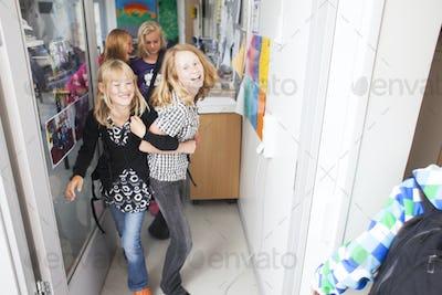 Mischievous schoolgirls leaving classroom