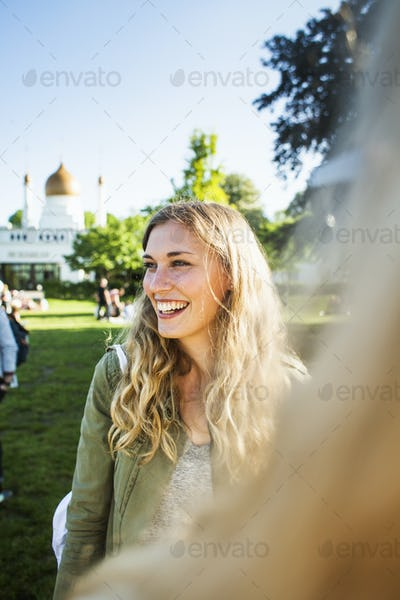 Cheerful woman looking away while standing with friend at park