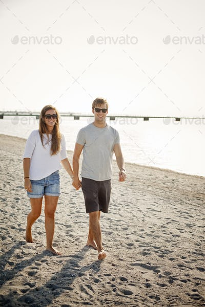 Full length of young couple holding hands while walking on shore