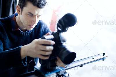 Close-up of man photographing through camera