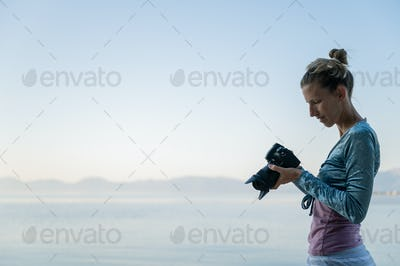 Female photographer checking setting on her camera