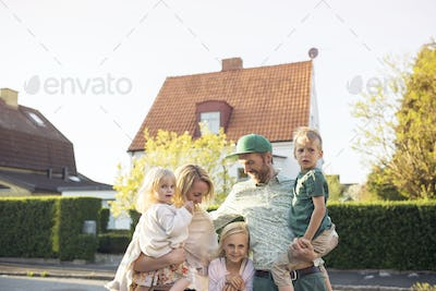 Family with children (18- 23 months, 4-5, 8-9 ) standing in in front of suburban house