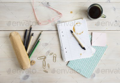 Stained notepad, coffee cup and pencil case on desk