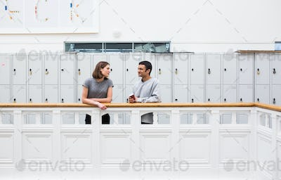 Two students (16-17) by railing in front of lockers
