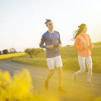 Two people running on country road
