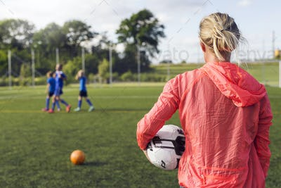 Mother looking at sons (10-11, 12-13, 14-15) during soccer practice