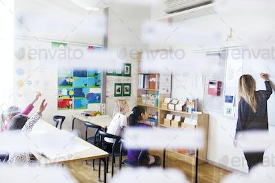Girls (8-9) looking at teacher in classroom