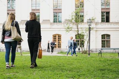 Two students (16-17) walking in schoolyard