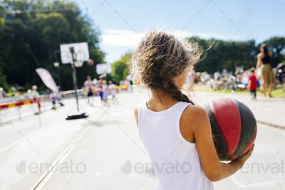 Rear view of girl (6-7) holding basketball