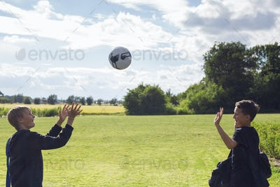 Two boys (12-13) throwing soccer ball in field
