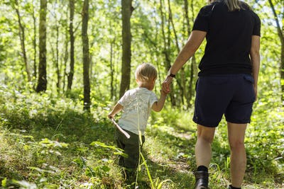 Boy (2-3) walking in forest with mother