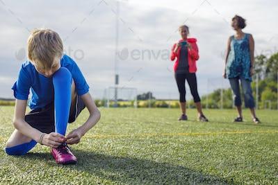 Boy (12-13) tying soccer shoes, two women in background