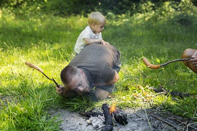 Man with son (2-3) igniting camp fire