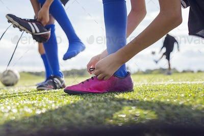 Boy tying soccer shoe