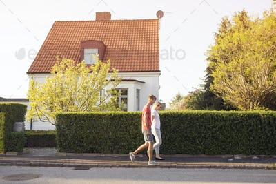Young man and young woman walking down suburban road