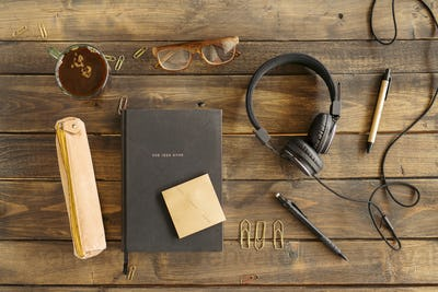 Office supplies, headphones, tea cup and notepad on desk