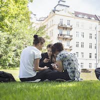 Teenage girls (14-15) and teenage boy (16-17) hanging out in park