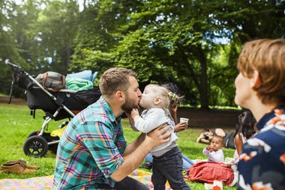 Father kissing daughter (2-3) during picnic