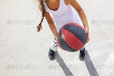 Low section of girl (6-7) holding basketball