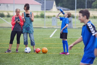 Mothers taking pictures of sons (10-11, 12-13) playing soccer