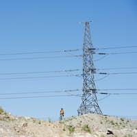 Man standing under electricity pylon