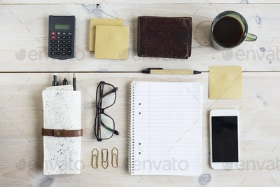 Office supplies, smart phone and coffee cup on desk