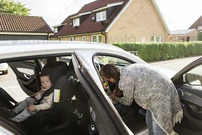 Mother fastening son's (18-23 months, 0-1 months) seat belt
