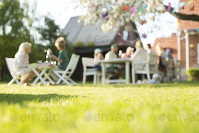 People sitting at tables at garden party