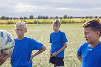 Boys (10-11, 12-13) standing in soccer field