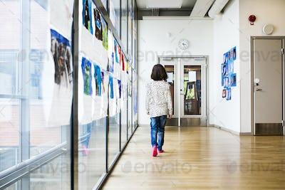 Girl (8-9) walking through school corridor