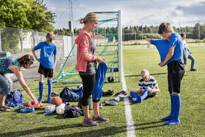 Mothers helping sons (10-11, 12-13) get dressed for soccer practice