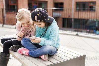 Girls (8-9) using mobile phone